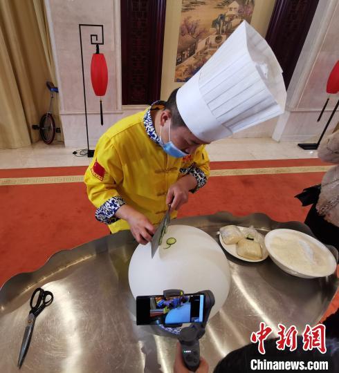 面艺师傅正在面气球上切黄瓜。 杨杰英 摄