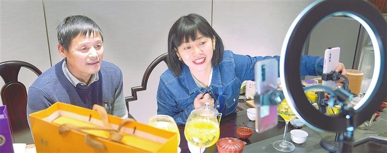 2020年12月16日,德安县吴山镇蔡河村老支书王冬生(左)正在学习直播销售金丝皇菊。