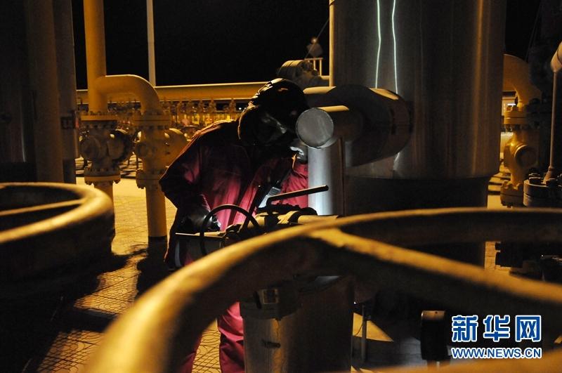1月6日,采气一厂区域中心监测员刘立伟在听管道是否存在漏气声音。新华社记者 王浡 摄