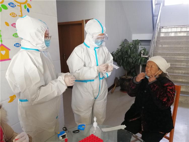 1月12日,志愿者刘亚静(左一)在河北广宗县刘全寨村为老人讲解核酸采样后居家隔离注意事项。