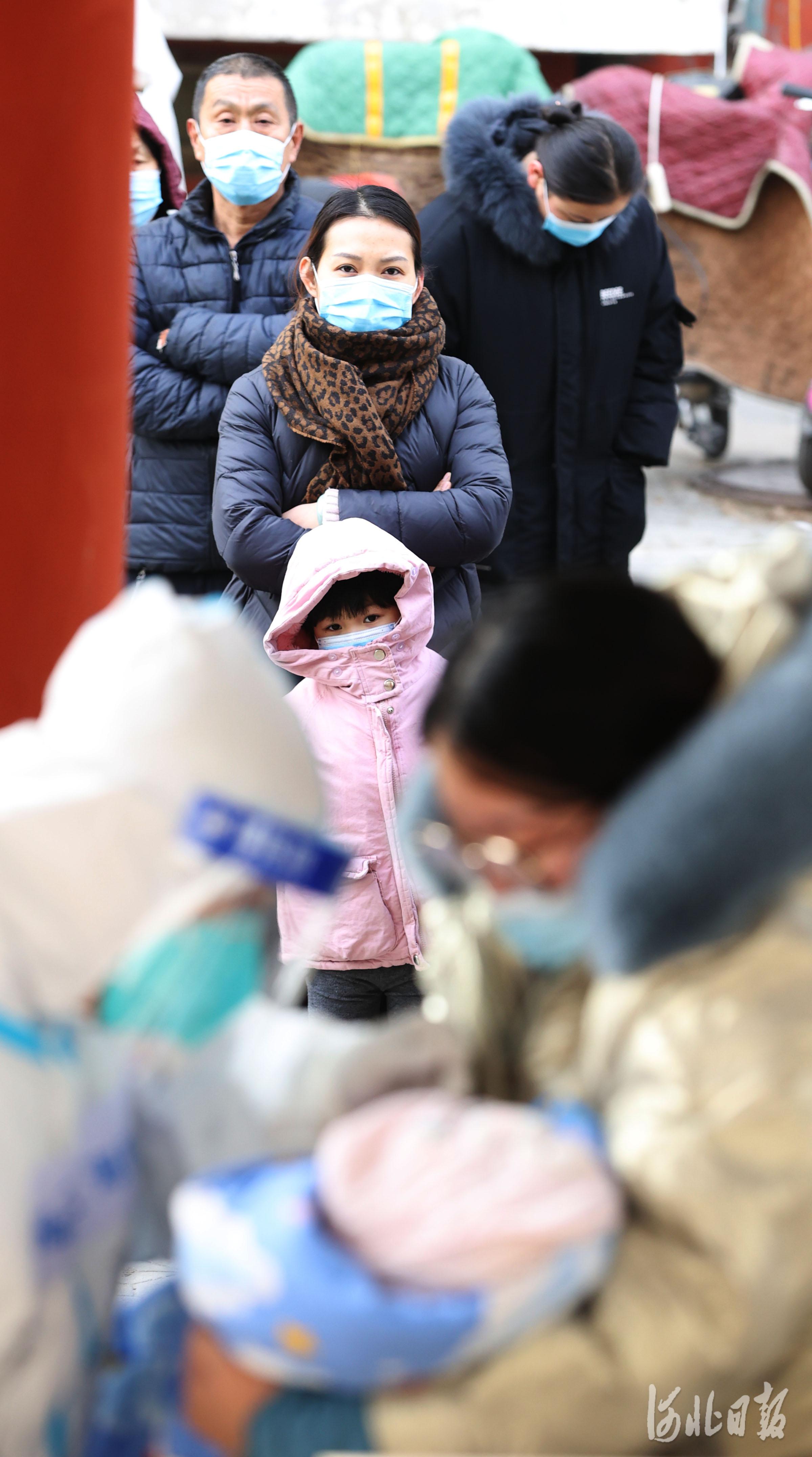 2021年1月12日,石家庄市新华区赵陵铺路街道党家庄社区的居民排队等待广东深圳核酸检测服务队进行核酸检测。
