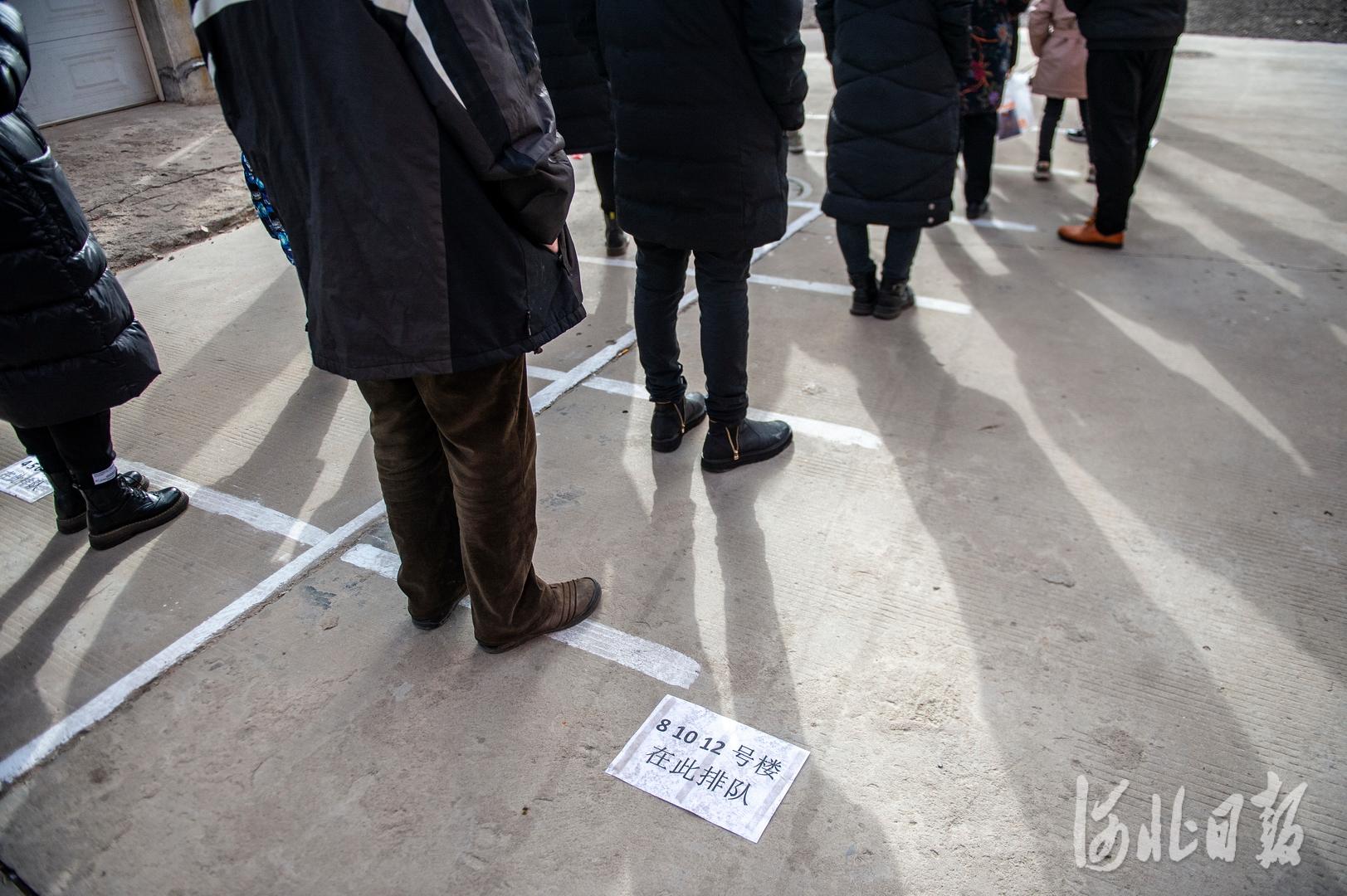 2021年1月12日,河北省石家庄市西古城社区,居民在社区工作人员和志愿者的引导下,排队等待接受第二次核酸检测采样。河北日报记者田明摄