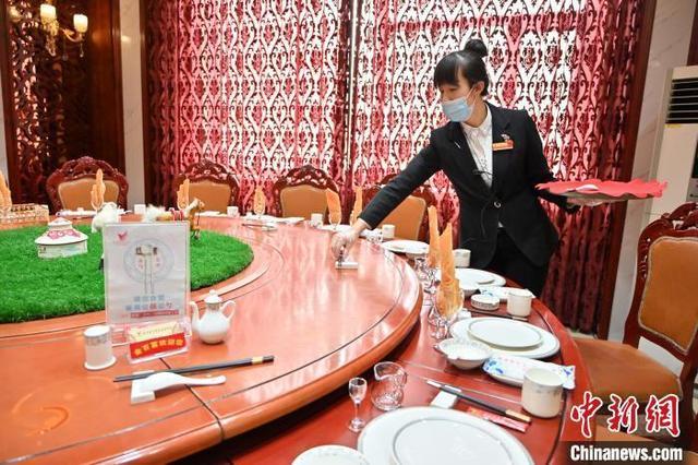资料图:2021年1月13日,呼和浩特某酒店工作人员在餐桌上摆放公筷。