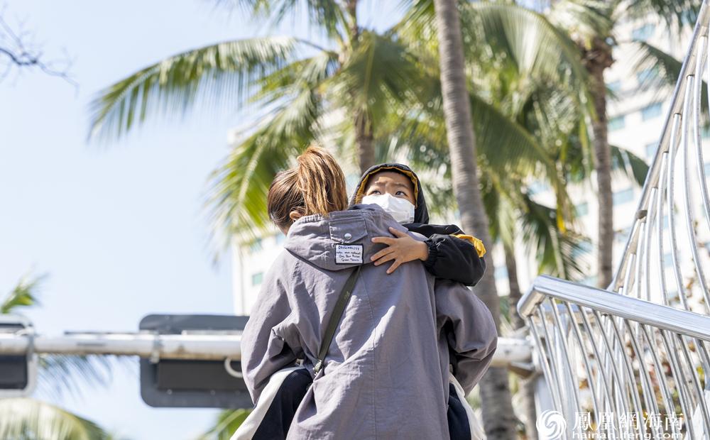 一位母亲怀抱着孩子走上天桥