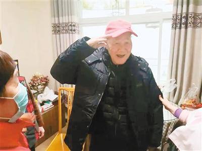 90岁老兵王立荣穿上志愿者送来的棉衣后,激动得敬礼表达谢意。 (莲湖区民政局 供图)