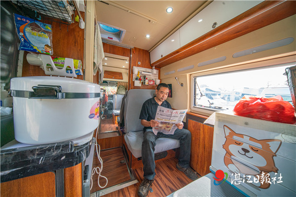 这名旅客正拿着《湛江日报》看新闻。