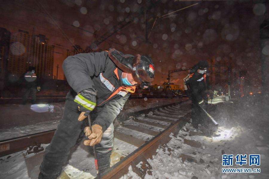 2月5日,在长春火车站,线路工张帅(右)、苏杰为轨道除雪。新华社记者 张楠 摄