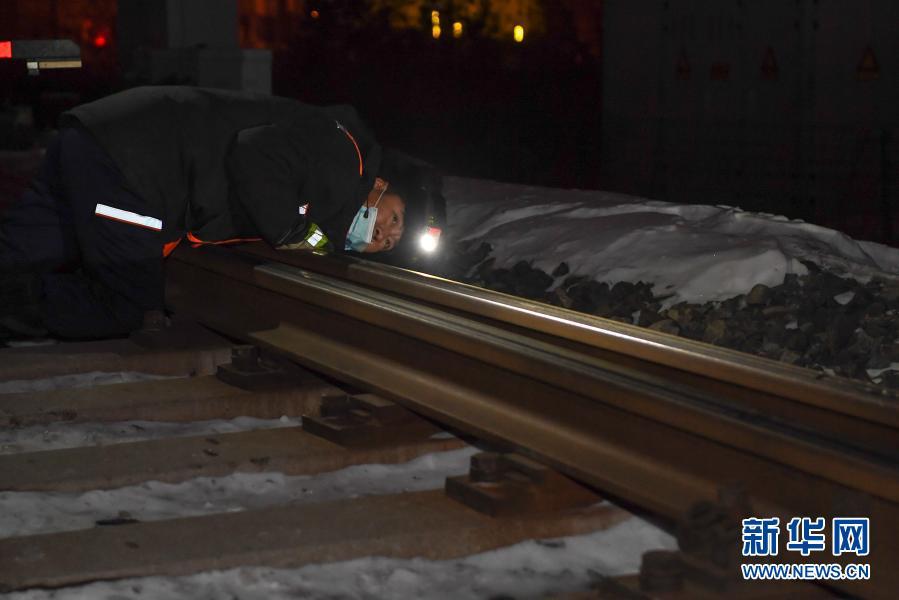 2月5日,在长春火车站,线路工王福民趴在地上查看轨道平整度。新华社记者 张楠