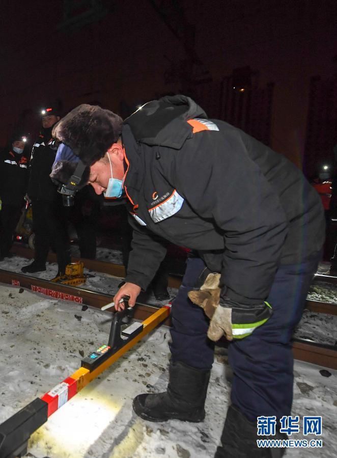 2月5日,在长春火车站,线路工王福民趴在地上查看轨道平整度。新华社记者 张楠 摄