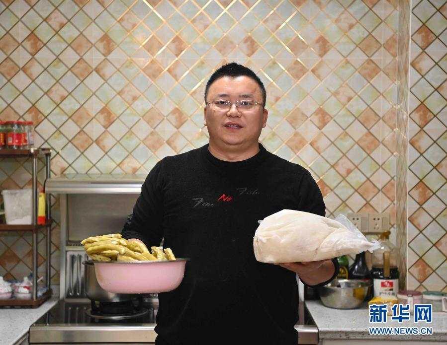 胡振在四川仁寿的家中展示家人为他准备的年货,他准备带这些到贵州去(2月15日摄)。