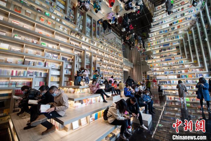 大读者、小读者或围坐在书桌前,或坐在台阶上,手捧一本书,沉浸在书香世界里。 韦亮 摄