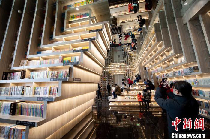 走进书店,镜面天花倒映着阶梯式书架,重塑层峦叠嶂的山峰,呈现出错落交织的视觉震撼。 韦亮 摄