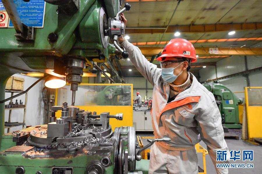 在中汽(天津)汽车装备有限公司车间,工人在用机器加工零件(2月14日摄)。