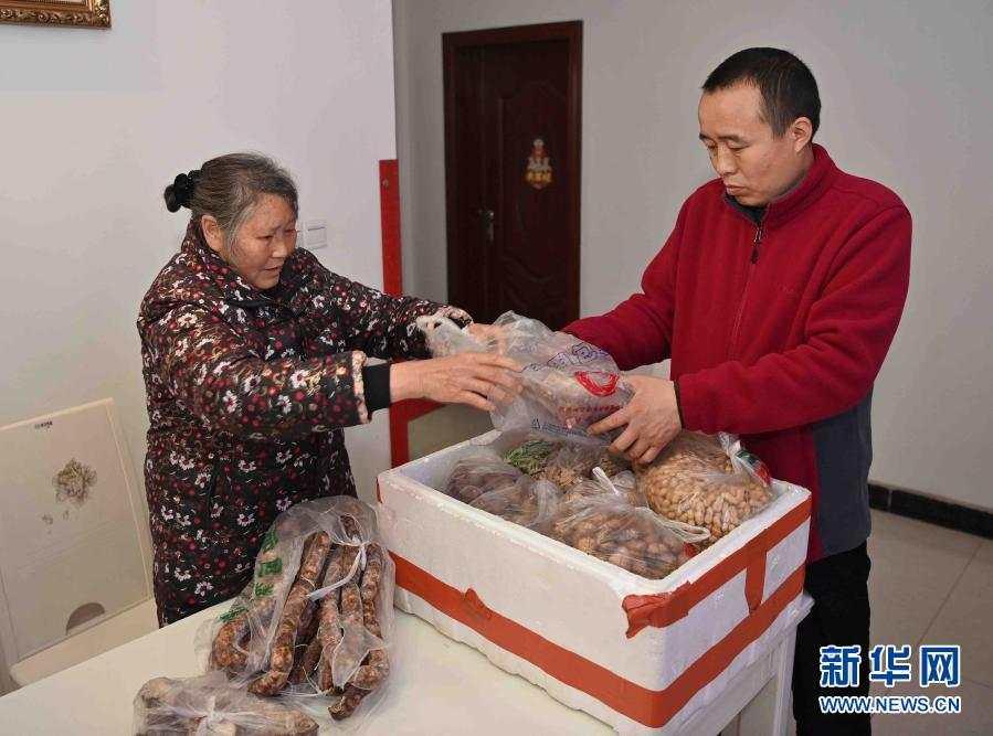 周茂勤(右)与家人在四川仁寿的家中收拾准备带到西藏那曲去的食物(2月15日摄)。