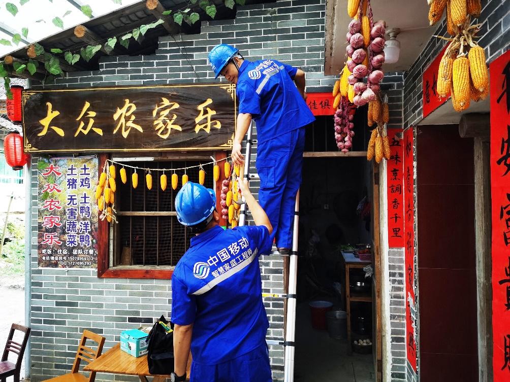 """中国移动智慧家庭工程师正在安装""""平安乡村""""摄像头。 徐先丽/摄"""