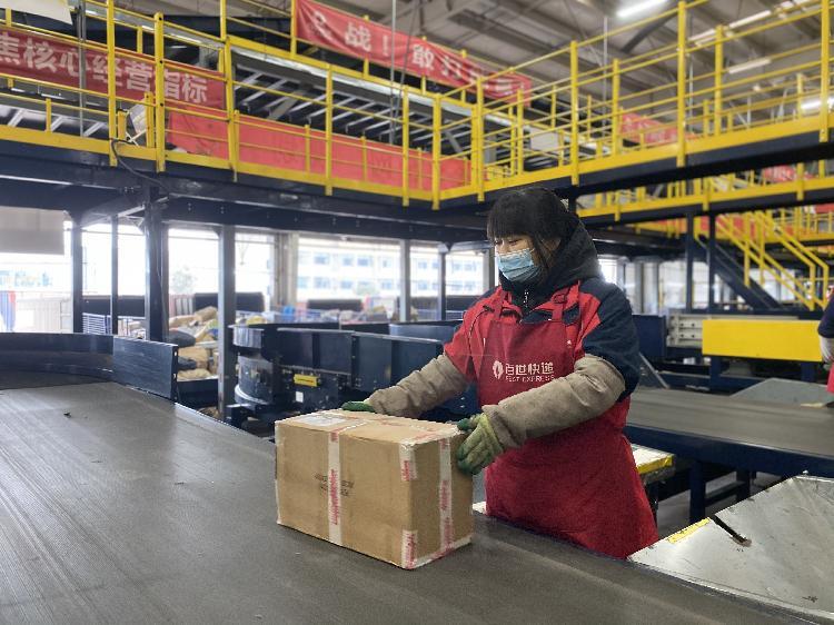 ▲ 渝北区通宝路,某快递重庆分拨中心,工作人员正忙着检查分拣包裹等。