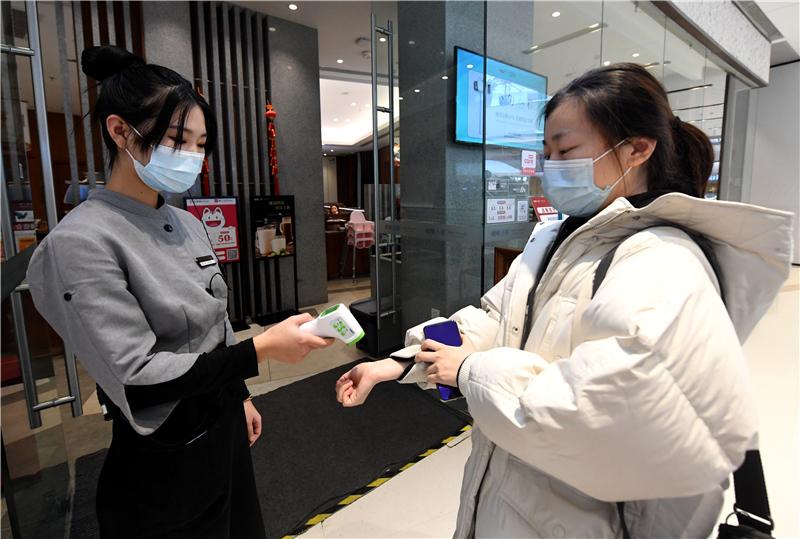 2月22日,在石家庄市桥西区华润万象城一家餐厅,工作人员(左)为准备进店的顾客测量体温。