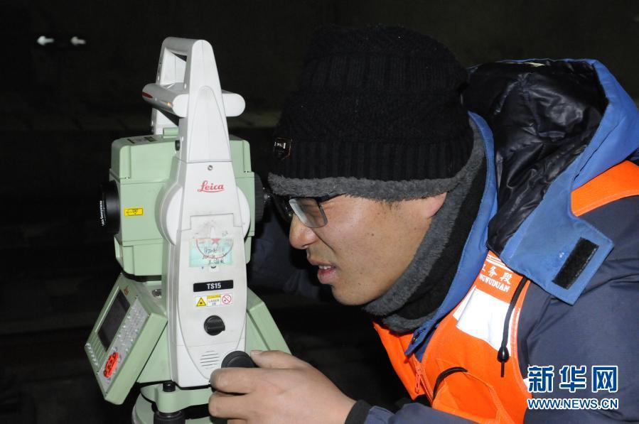 2月21日,工人通过光学全站仪进行检查任务。新华社记者 王浡 摄