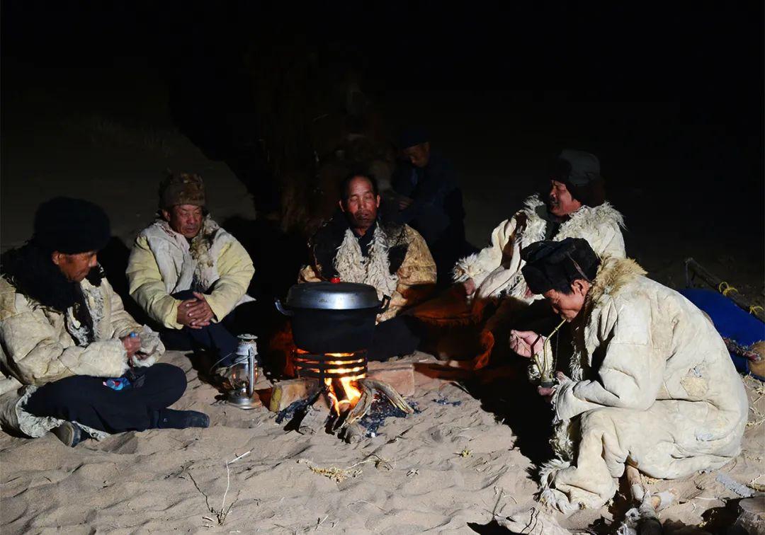 ▲ 野外宿营:深入腾格里沙漠腹地驮运沙漠特产的张元生驼队夜晚在沙丘宿营。李军摄于2016年10月21日