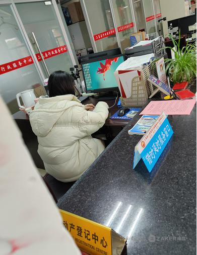"""▲ """" 不动产一窗受理 """"1 号窗口,一名工作人员在玩手机。"""