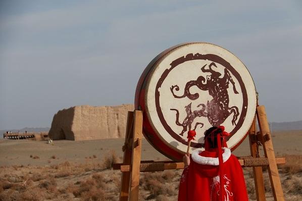 工作人员在在世界文化遗产玉门关遗址为游客表演大汉战鼓
