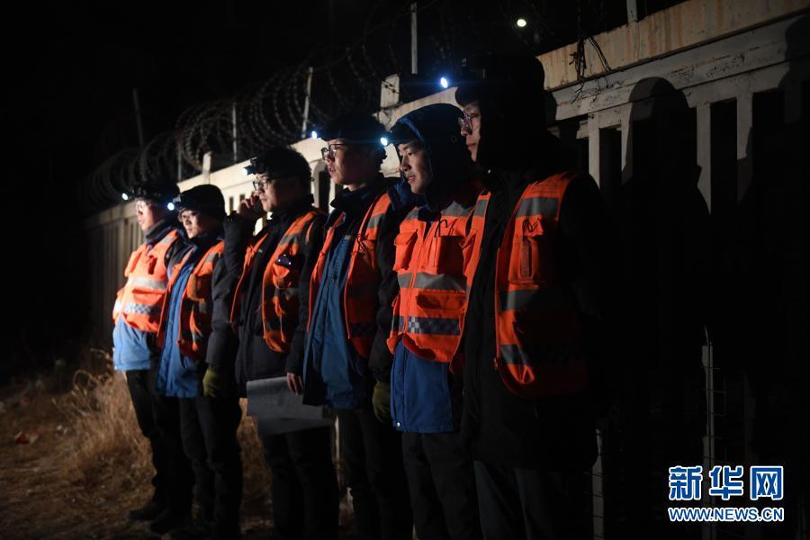 2月21日,夜幕下工人们集合准备出发。新华社记者 张曼怡 摄