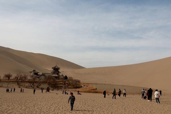 游客在鸣沙山月牙泉景区游览