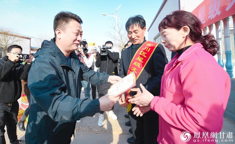 金川区委副书记、区长张恒山(前左)为高立军夫妇颁发星级文明户标兵荣誉证书 杨艺锴 摄