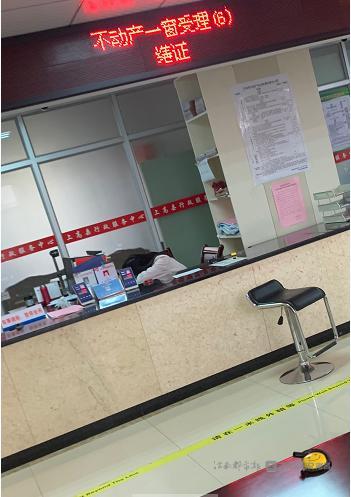 """▲ """" 不动产一窗受理 """"6 号窗口工作人员正在睡觉。"""