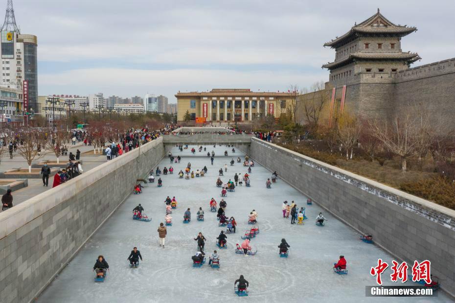 2月19日,山西大同,民众大同古城外的护城河天然冰场上滑冰车玩耍,享受冰上运动的乐趣。中新社记者 武俊杰 摄