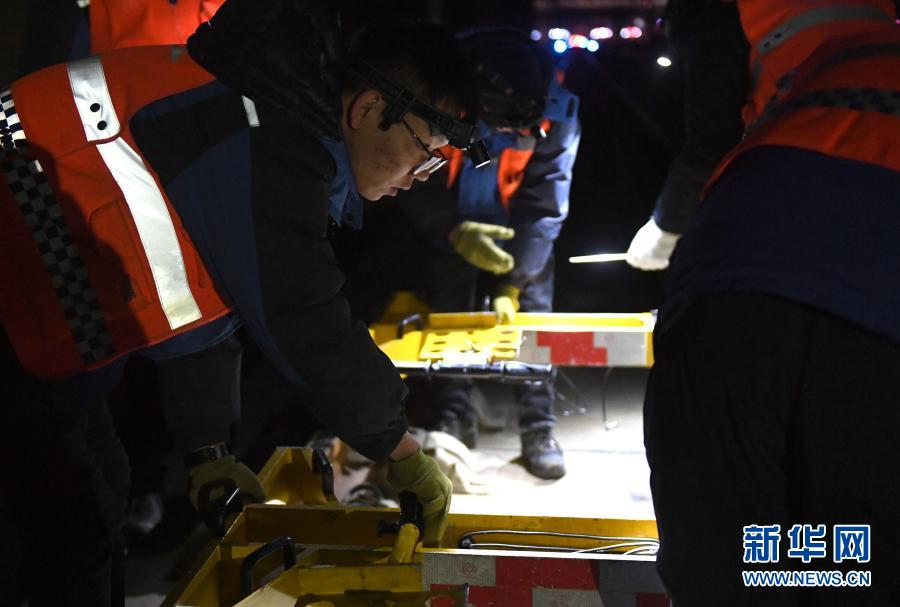 2月21日,工人们在安装检查设备。新华社记者 张曼怡 摄