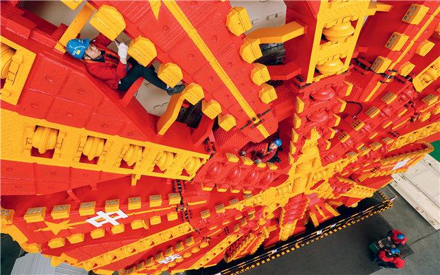 (在铁建重工位于湖南长沙的生产车间里,工作人员钻进一台巨大的盾构机刀盘的缝隙里,进行检查。马宏杰 摄)