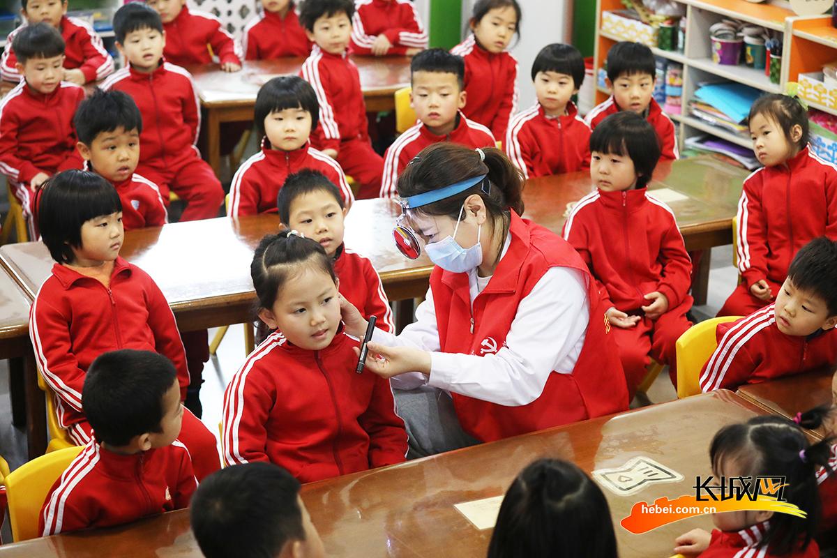3月3日,在丰润区光华道幼儿园,医生志愿者为小朋友进行耳道检测。朱大勇 摄