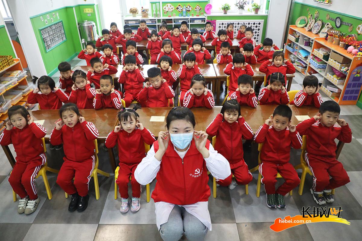 3月3日,在丰润区光华道幼儿园,医生志愿者教小朋友们做耳保健操。朱大勇 摄