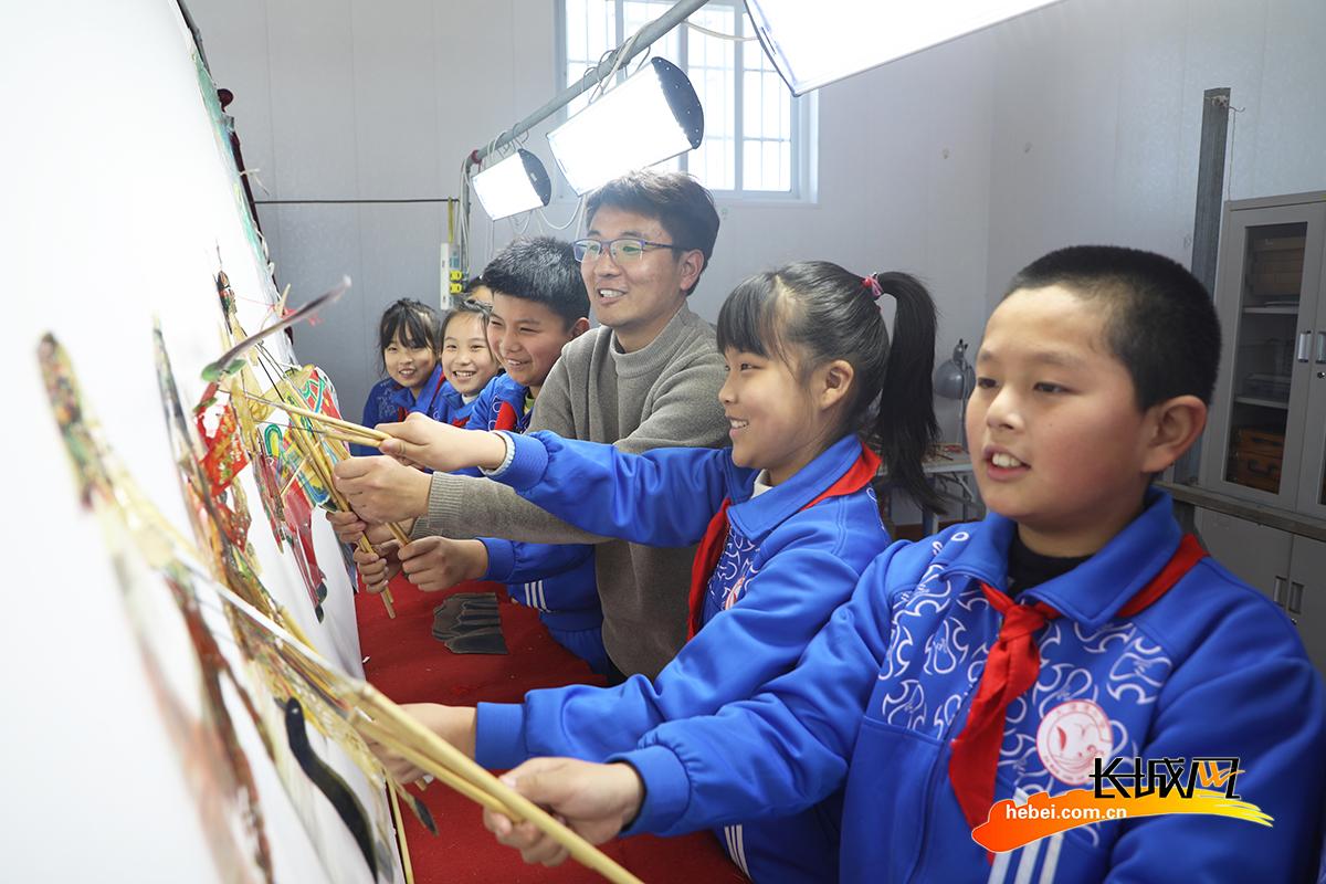 3月1日,丰润区李钊庄镇大漫港小学老师在辅导学生表演皮影戏。朱大勇 摄