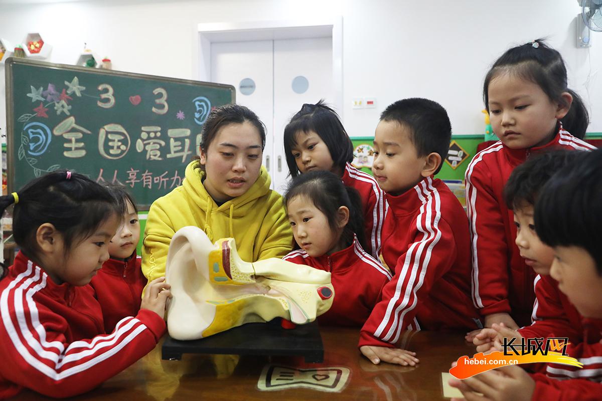 3月3日,在丰润区光华道幼儿园,医生志愿者利用耳朵构造模型向小朋友讲解爱耳护耳保健知识。朱大勇 摄