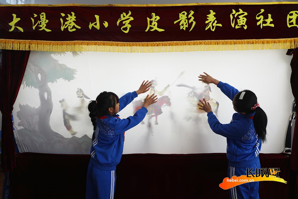 3月1日,丰润区李钊庄镇大漫港小学学生在观看皮影戏表演。朱大勇 摄