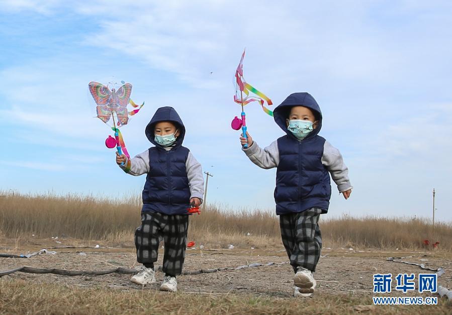 双胞胎男孩举着风筝,也是一道风景。(史港泽 摄)