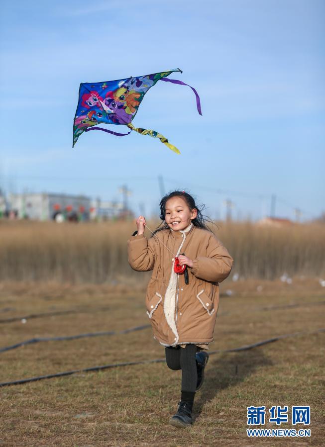 一个小姑娘随风奔跑,脸上洋溢着开心的笑容。(史港泽 摄)