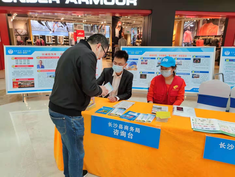 长沙县商务局工作人员在向市民解读相关政策。