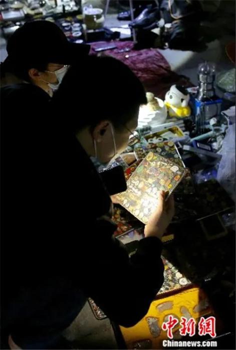 """4月2日晚,一位买家在""""鬼市""""摊位前拿着手电仔细查看货品。<a target='_blank' href='http://www.chinanews.com/'>中新社</a>易海菲 摄"""