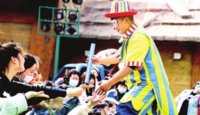 方特欢乐世界里,小丑演员与游客有趣互动。