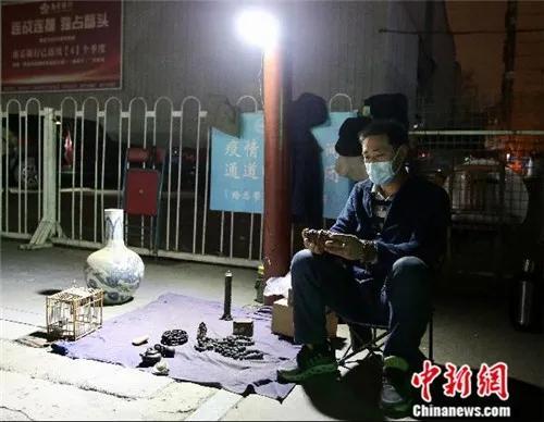4月2日晚,魏根华在摊位前休息。由于小雨,他已把摊位上的部分货品收起。<a target='_blank' href='http://www.chinanews.com/'>中新社</a>易海菲 摄