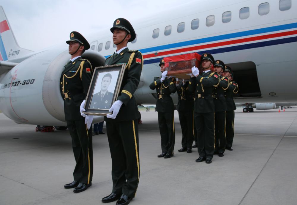2016年6月9日下午,我赴马里维和部队遇袭伤亡人员回国迎接仪式在吉林省长春市龙嘉机场举行。图为礼兵护送申亮亮的灵柩下飞机。