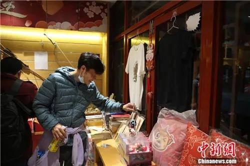 4月2日晚,一位顾客在潘家园文创商店内挑选商品。<a target='_blank' href='http://www.chinanews.com/'>中新社</a>易海菲 摄