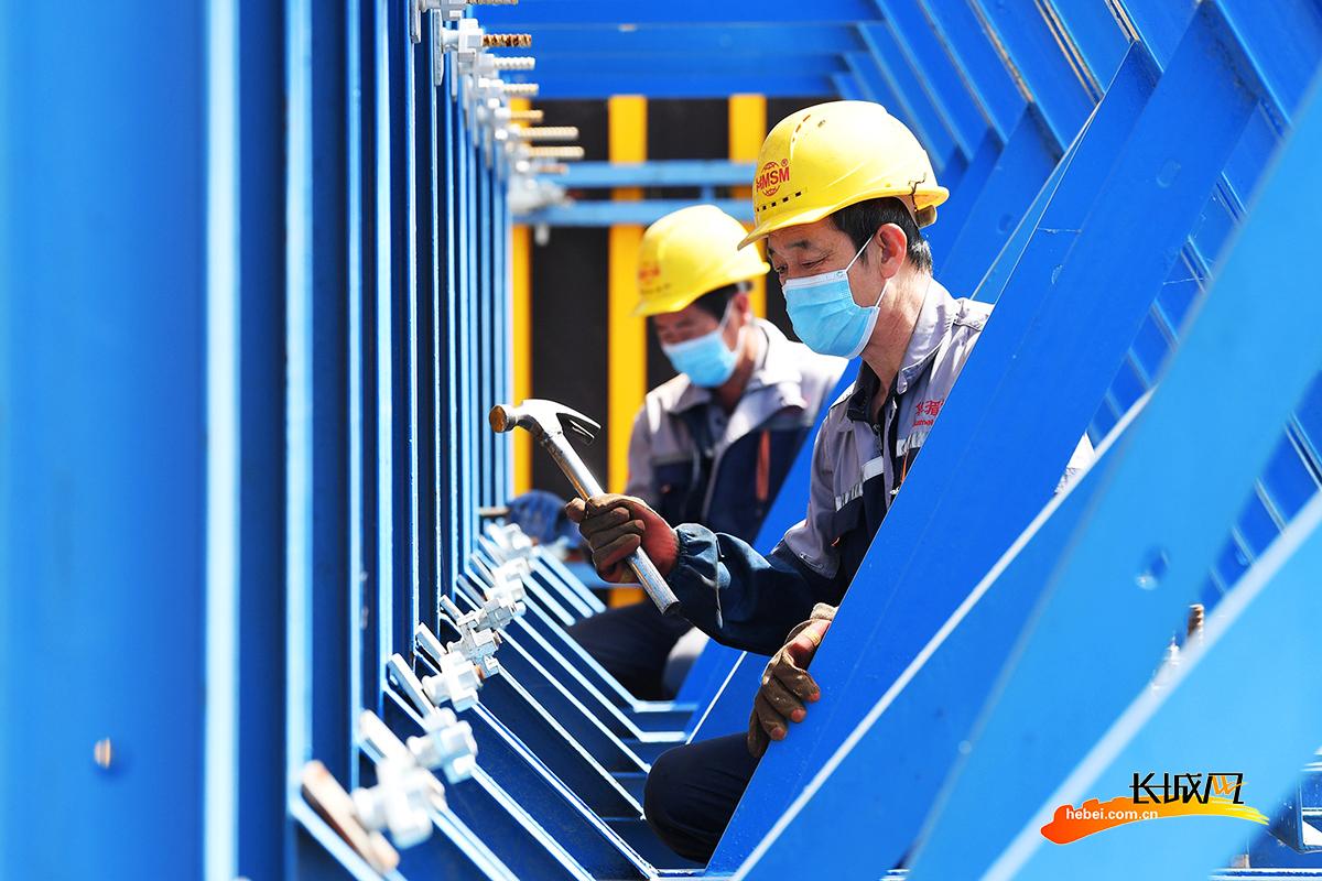 由北京转移到该县的一家建筑支护设备生产企业的工人在加工桥梁用大型模板。