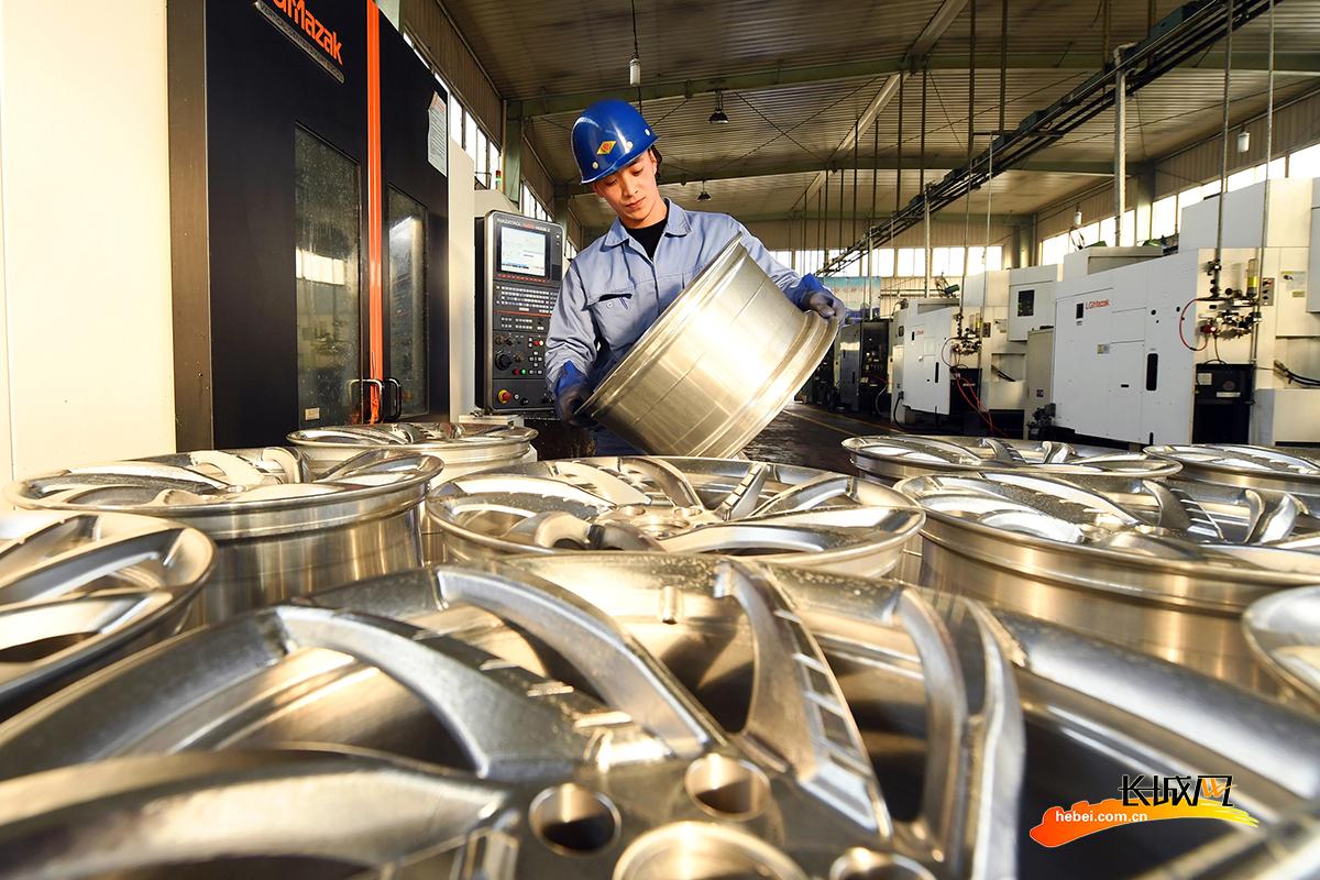 该县一家汽车配件制造企业的工人在检验下线的汽车轮毂质量。