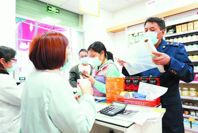 在药品商店内查看商户使用的塑料袋是否符合规定,并向商户进行相关条例宣传