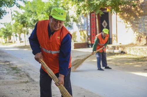 在深州市大堤镇马家口村,环卫人员在清扫街道。 新华社记者李晓果摄