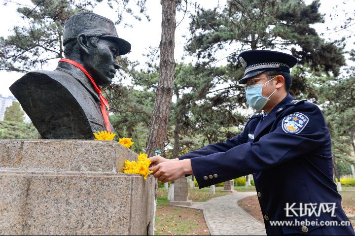民警向烈士雕像献花。